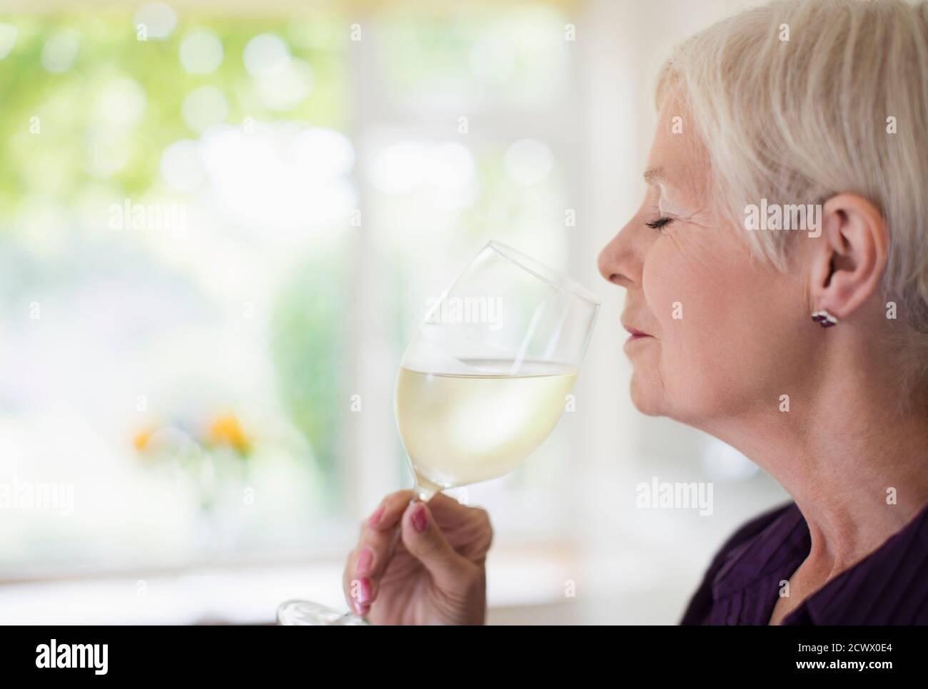 Femme sénior sentant et goûtant du vin blanc Banque D'Images