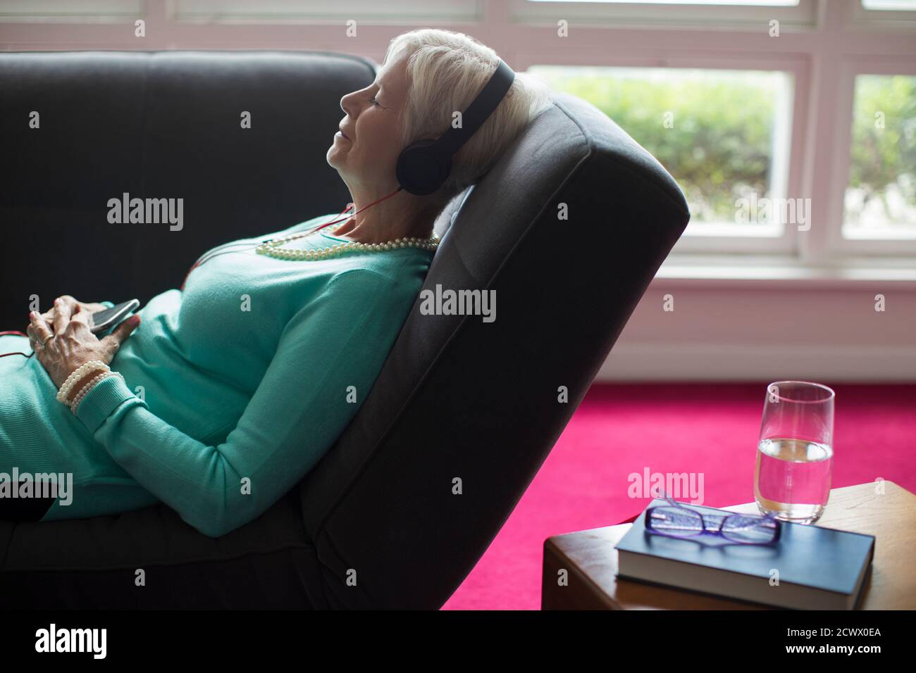 Femme sénior écoutant de la musique avec un casque sur le canapé Banque D'Images