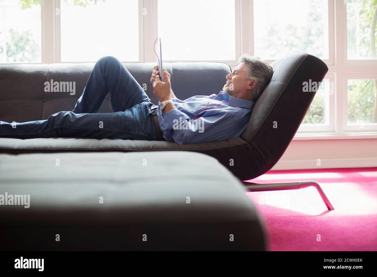 Homme senior se détendant avec une tablette numérique sur le canapé du salon Banque D'Images