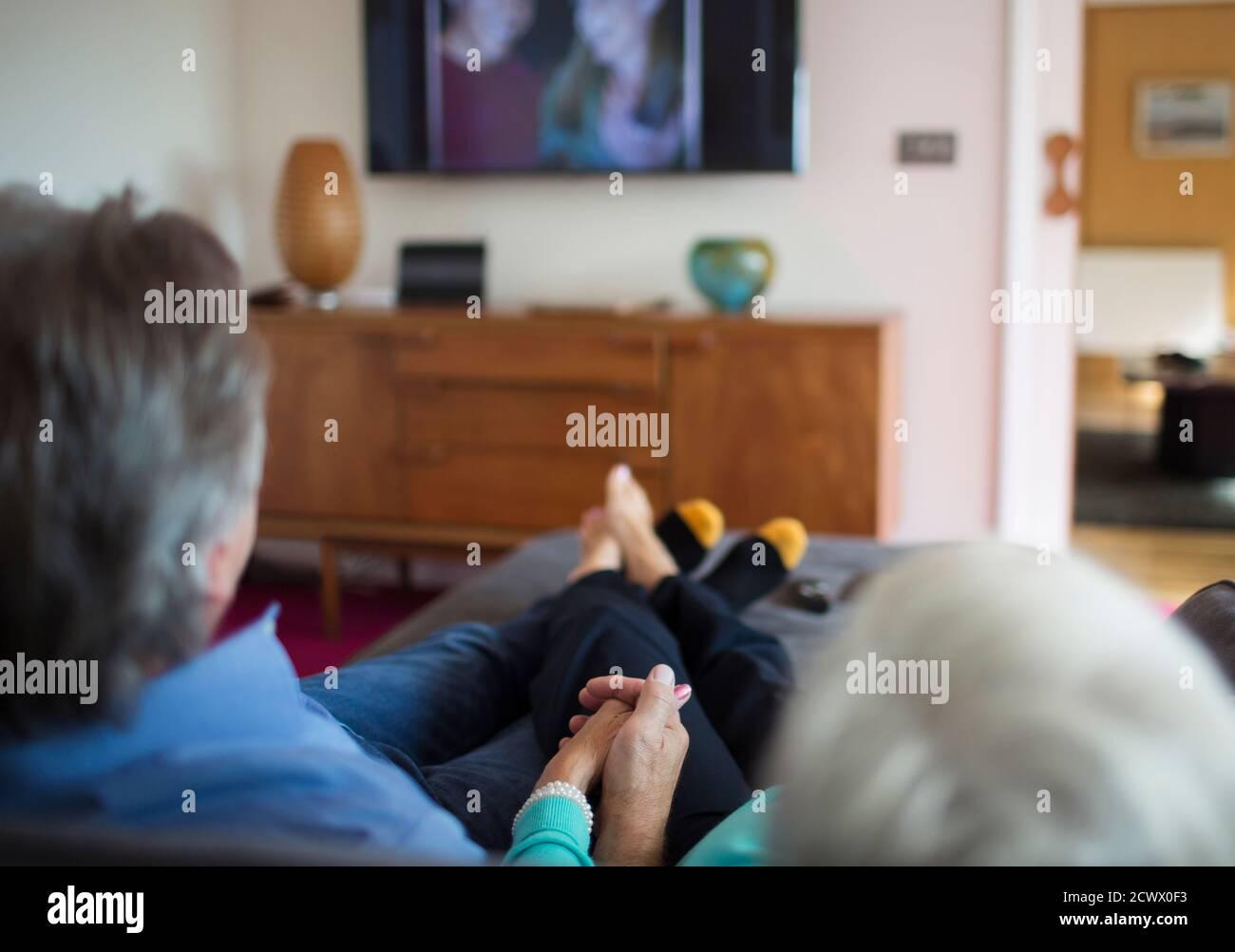 Couple senior tenant les mains et regardant la télévision dans le salon canapé Banque D'Images