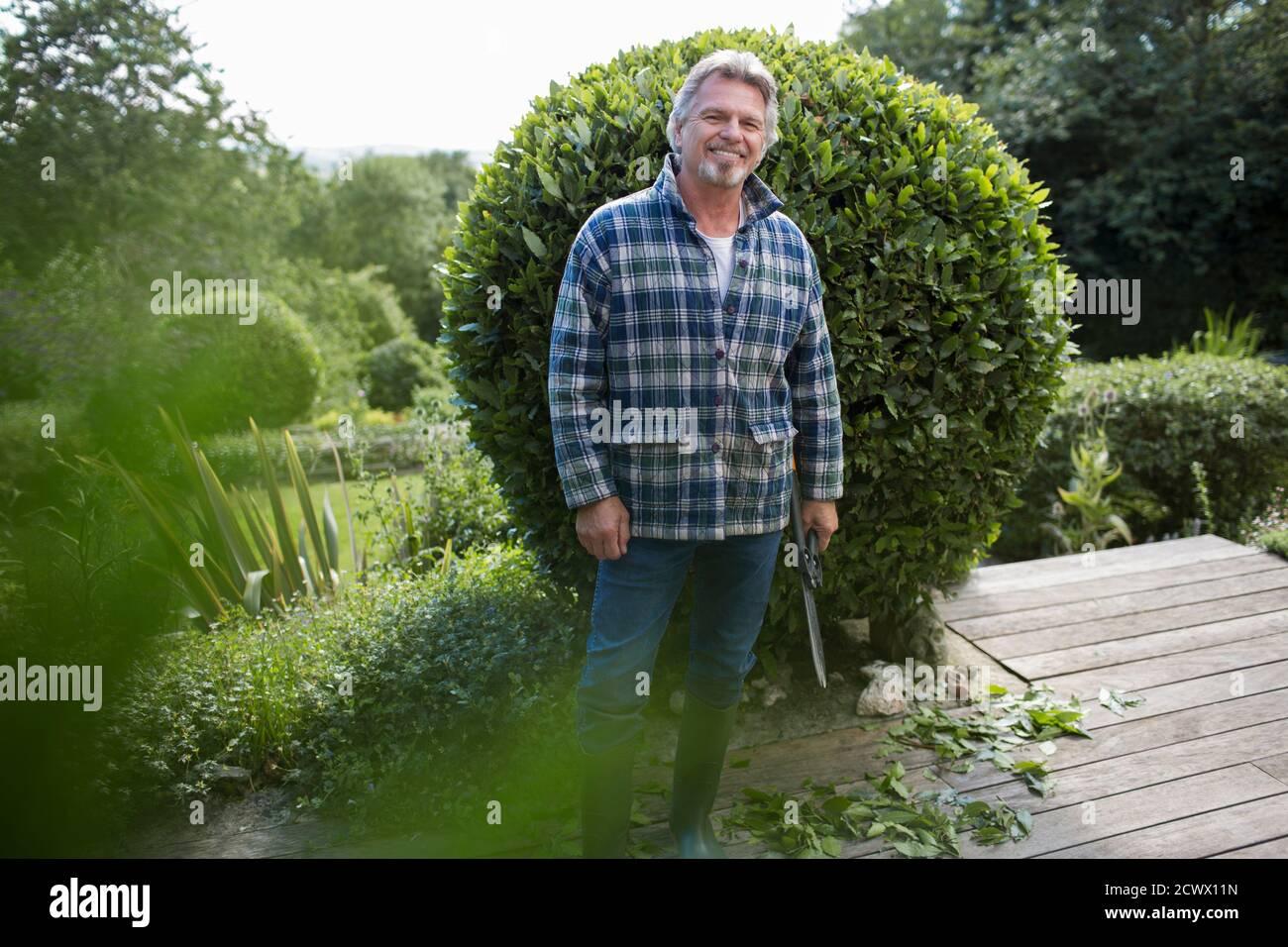 Portrait bon homme âgé jardinant sur le patio Banque D'Images