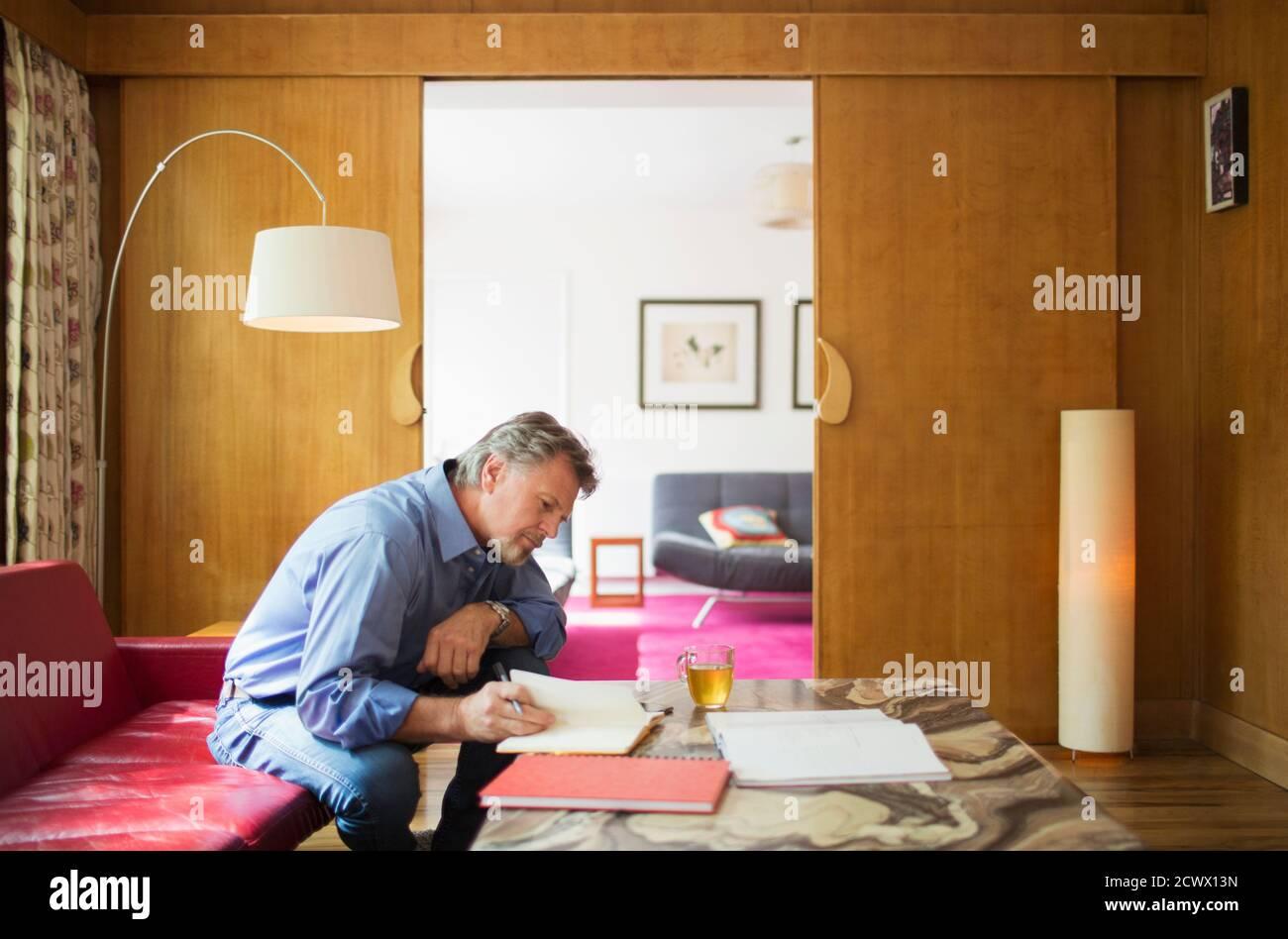 Homme âgé avec ordinateur portable travaillant dans le salon Banque D'Images