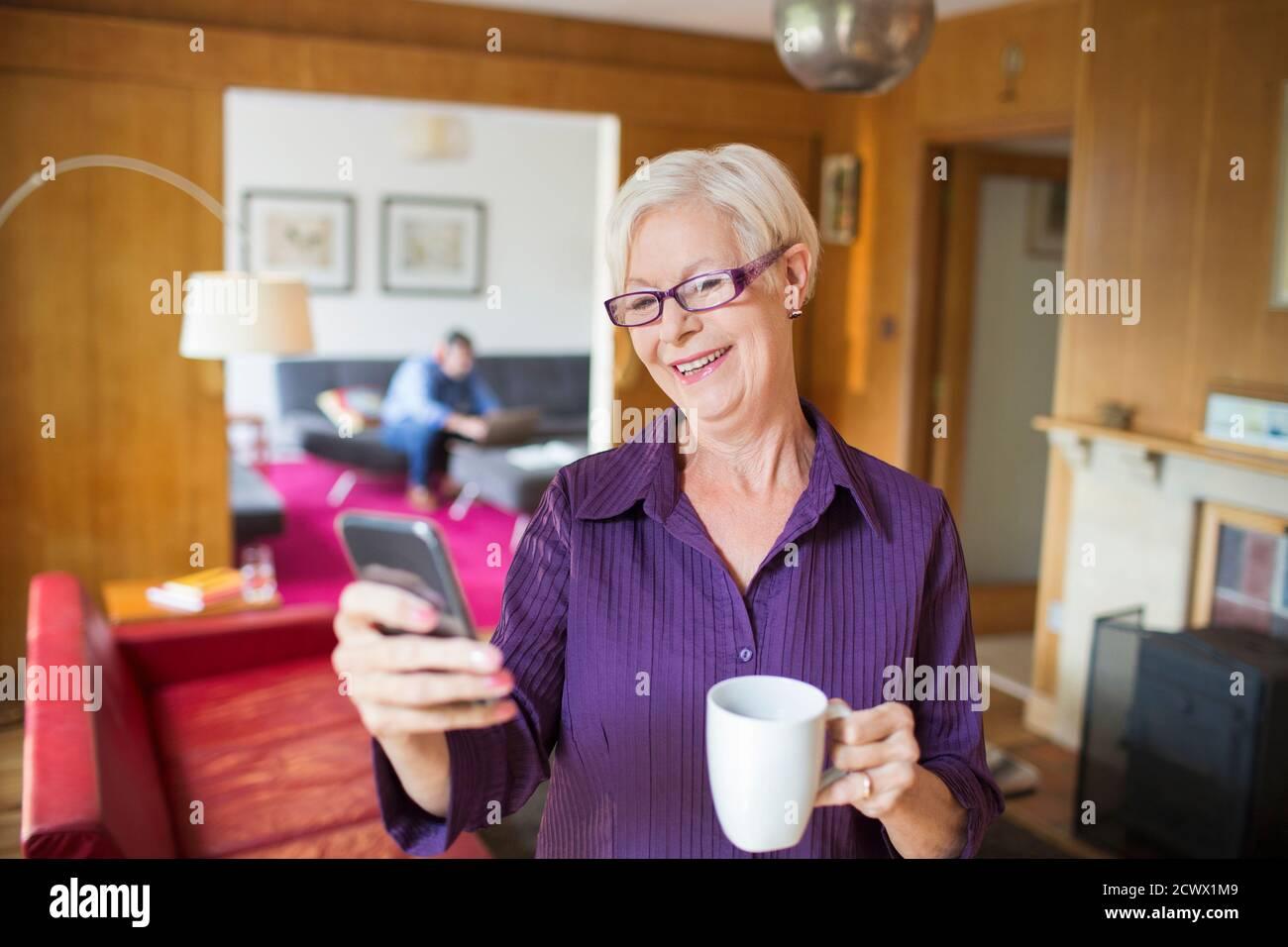 Bonne femme âgée utilisant un smartphone et prenant du thé séjour Banque D'Images