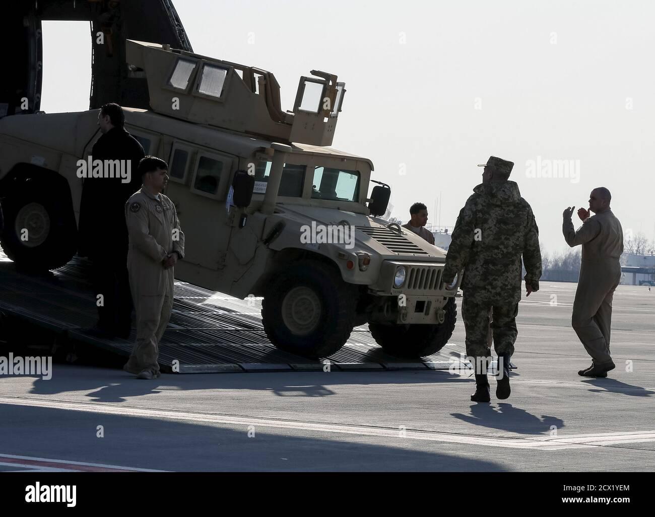 Un militaire ukrainien (2e R) considère comme le premier avion des États-Unis avec une aide non létale, dont dix véhicules Humvee, est déchargé à l'aéroport de Borispol près de Kiev, le 25 mars 2015. Les États-Unis ont envoyé une aide non létale supplémentaire à l'Ukraine, y compris des drones non armés et des véhicules Humvee, a déclaré un responsable de la défense des États-Unis le 11 mars. Le responsable, s'exprimant à condition d'anonymat, a déclaré que certaines parties du paquet américain, y compris 30 Humvees fortifiés avec une armure supplémentaire, pourraient venir en quelques semaines, tandis que d'autres parties pourraient prendre plus de temps. L'aide intervient alors que l'Ukraine lutte contre une rébellion soutenue par la Russie Banque D'Images