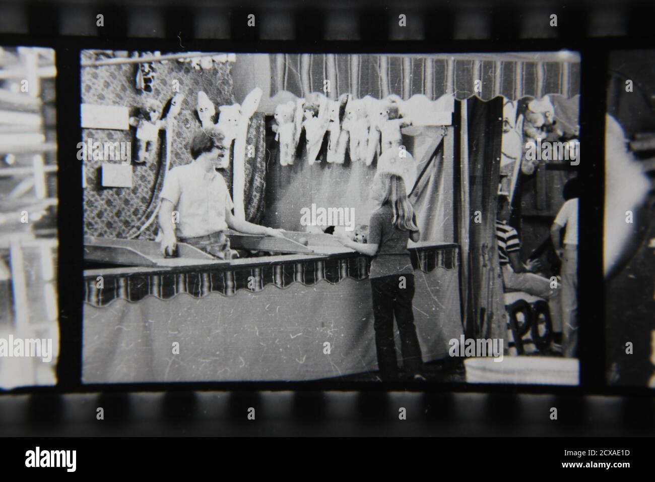 Belle photographie en noir et blanc vintage des années 1970 d'un type régulier qui occupe un stand de jeu de carnaval lors d'une foire de rue de carnaval. Banque D'Images