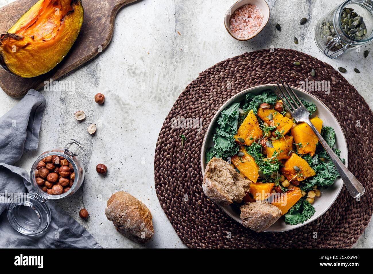 Vue de dessus de salade de saison avec citrouille grillée, chou frisé, pois chiches, pepitas et noix. Recette végétarienne d'automne saine. Banque D'Images