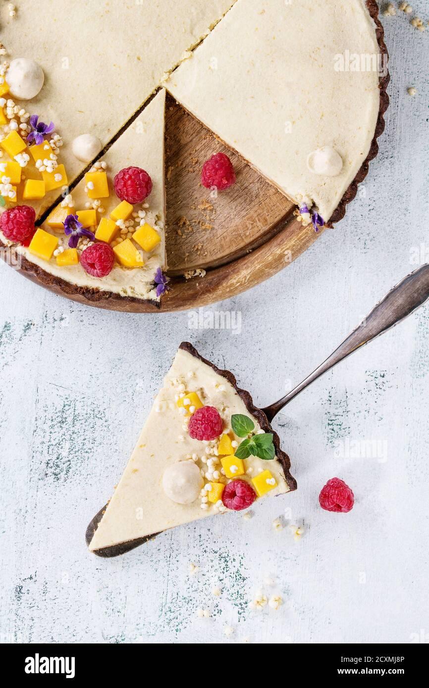 Des tranches de tarte au chocolat décoré par la mangue, framboises, menthe, riz soufflé et fleurs comestibles avec morceau de gâteau sur une pelle à tarte sur texte blanc Banque D'Images