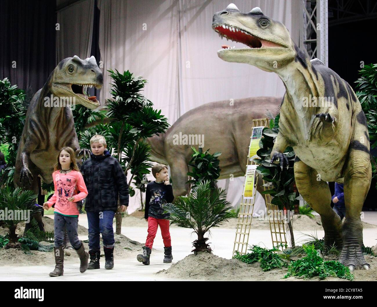 """Children walk by life-sized Ceratosaurus dinosaur models in Vienna February 7, 2014. The travelling exhibition """"World of Dinosaurs"""" shows some 50 life-sized dinosaur models and runs in Vienna until February 23. REUTERS/Heinz-Peter Bader  (AUSTRIA - Tags: SCIENCE TECHNOLOGY SOCIETY) Banque D'Images"""