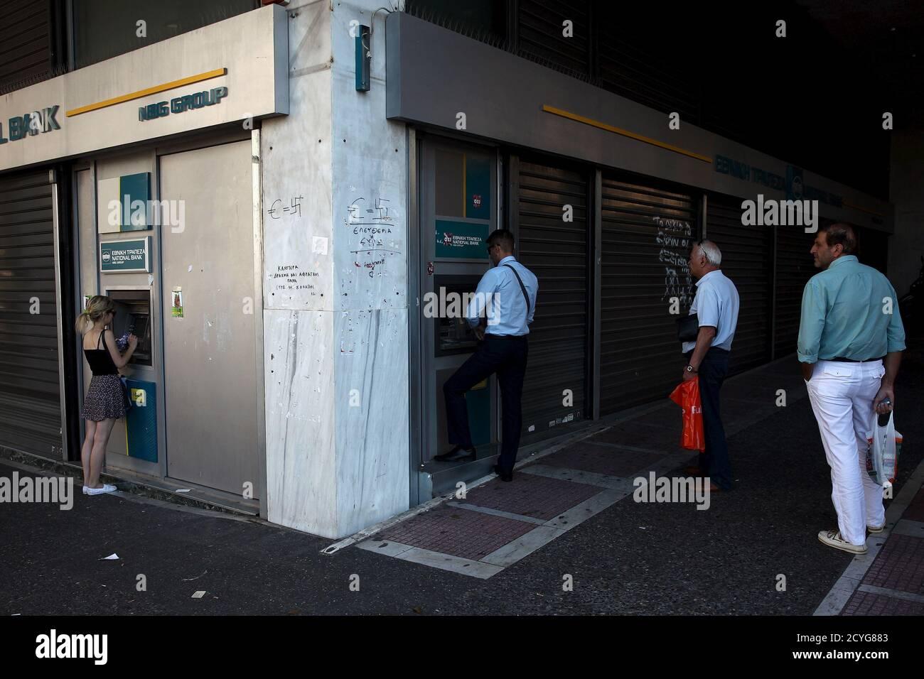 Les gens font la queue pour retirer de l'argent d'un guichet automatique (ATM) à l'extérieur d'une succursale de la Banque nationale à Athènes, Grèce le 17 juillet 2015. Un haut fonctionnaire grec a confirmé jeudi que les banques rouvriraient lundi et a déclaré que le gouvernement cherchait à permettre aux gens de procéder à des retraits de 60 euros sur plusieurs jours. REUTERS/Yiannis Kourtoglou Banque D'Images
