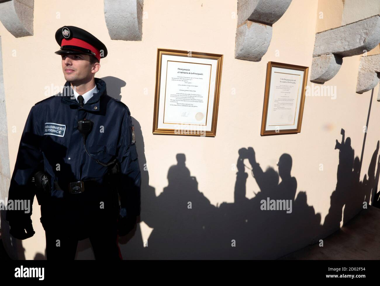 Shadows of photographers are cast on the wall near a carabinieri who stands next to the official declaration of Prince Albert II announcing the birth of twins to the Prince and Princess Charlene, at Monaco Palace December 11, 2014. Princess Charlene of Monaco gave birth on Wednesday to a boy and a girl, the royal couple's first children, an aide to the royals said. According to Monaco's Constitution the boy, named Jacques, will be first-in-line to the throne, and not his twin sister, Gabriella.  REUTERS/Eric Gaillard (MONACO - Tags: ROYALS ENTERTAINMENT) Banque D'Images