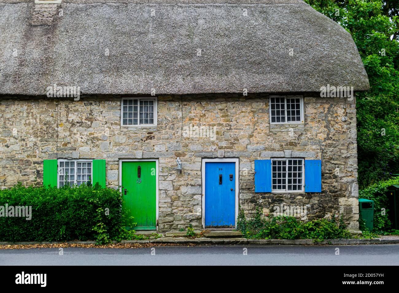 West Lulworth, Royaume-Uni - 19 juillet 2020: Belle maison de campagne en chaume avec portes et volets bleus et verts, couleur Dorset unique Banque D'Images