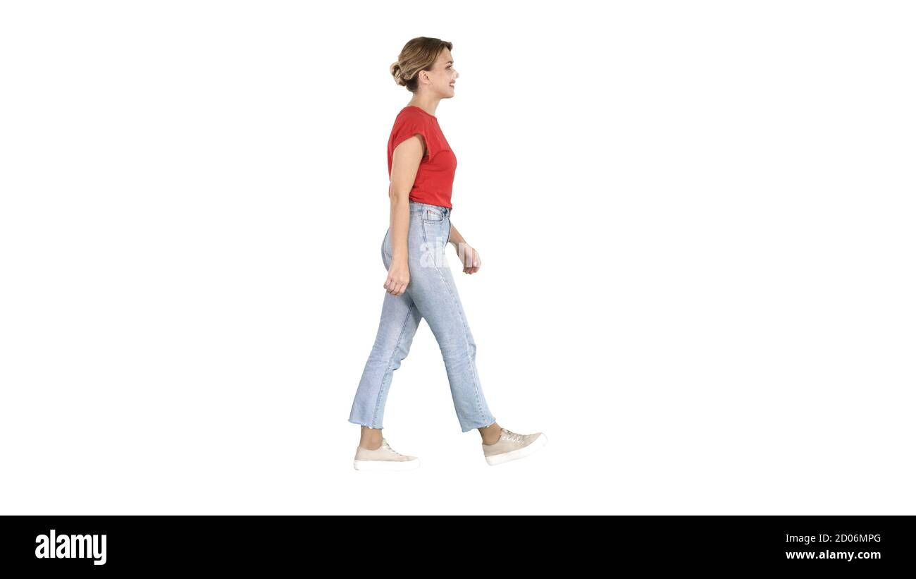 Femme en t-shirt rouge, jeans et baskets marchant sur le dos blanc Banque D'Images