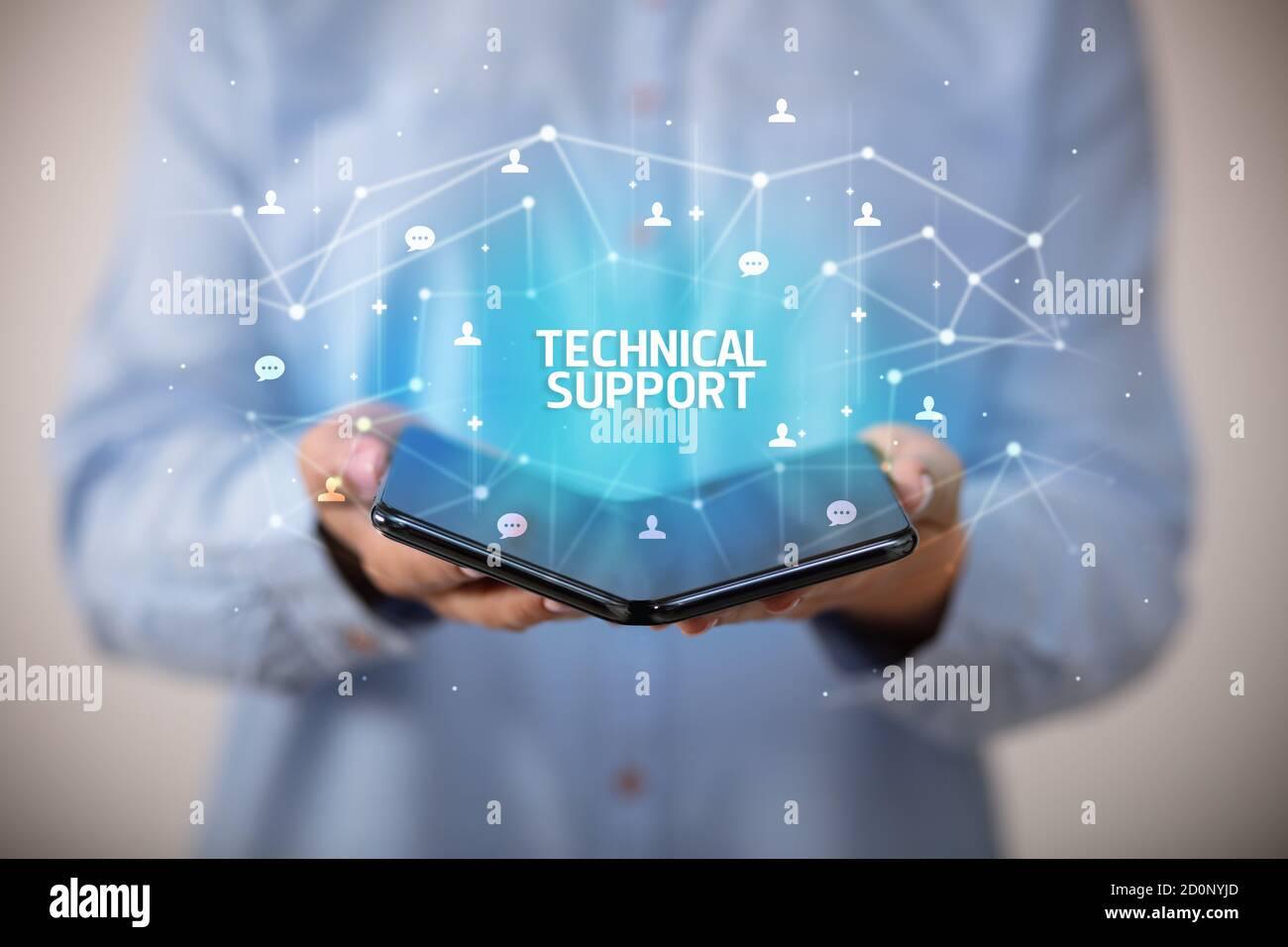Businessman holding a smartphone pliable avec le soutien technique de l'inscription, la nouvelle technologie concept Banque D'Images