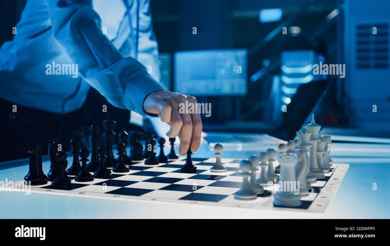 Gros plan d'une intelligence artificielle fonctionnant un bras robotique futuriste dans un jeu d'échecs contre un humain. Le robot déplace un Pawn. Ils sont dans un Banque D'Images