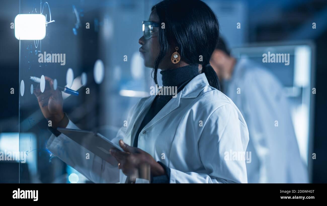 Dans le laboratoire de recherche Smart et belle Afro-américaine femelle Un scientifique portant un manteau blanc et des lunettes de protection écrit Formula on Verre Banque D'Images