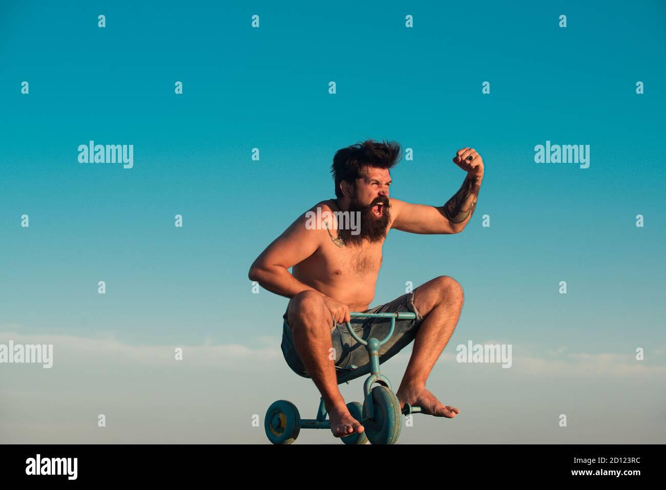 Guy tricycle d'équitation pour enfants. Portrait d'un homme barbu comme un hipster fou s'amusant avec le vélo dehors. Un jeune homme excités qui fait un petit vélo Banque D'Images