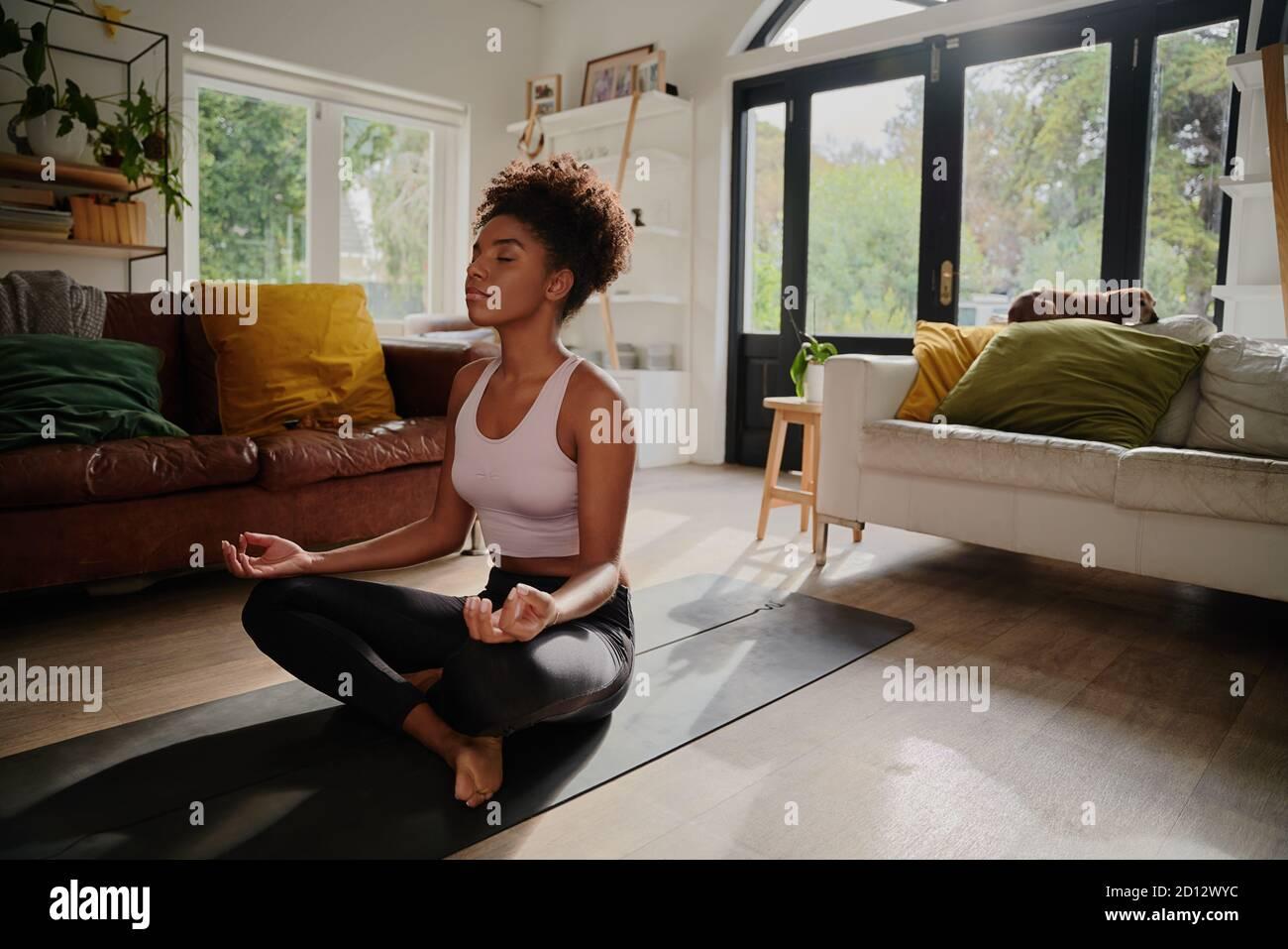Jeune femme africaine méditant assise en position lotus à la maison sur le tapis de yoga Banque D'Images