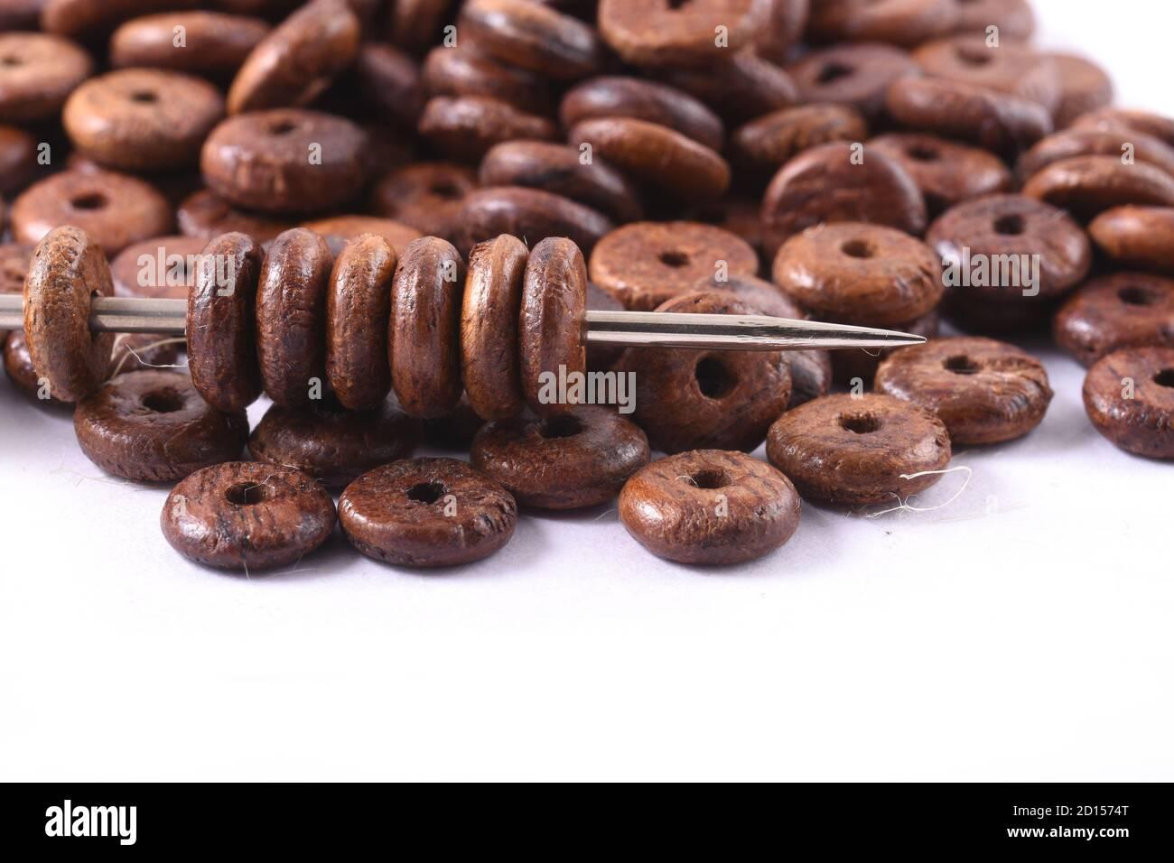 Perles de bois étalés sur fond blanc avec aiguille. Perles avec aiguille . Gros plan, macro. Banque D'Images