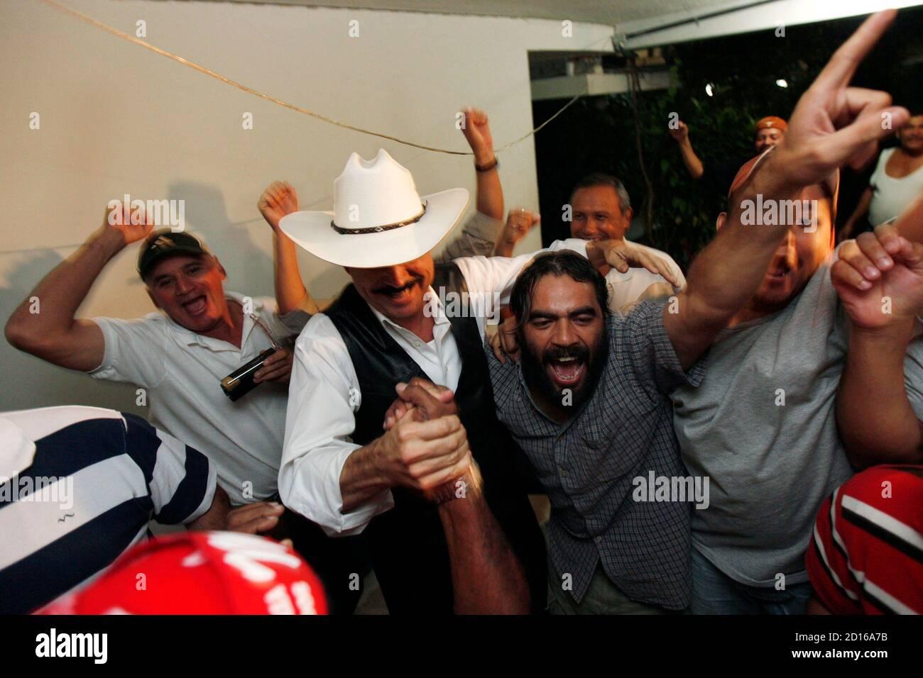 Ousted Honduras' President Manuel Zelaya (C) celebrates with supporters after Honduras' 2010 World Cup qualifying match victory over El Salvador, inside the Brazilian embassy in Tegucigalpa October 14, 2009. REUTERS/Edgard Garrido (HONDURAS POLITICS SPORT) Banque D'Images