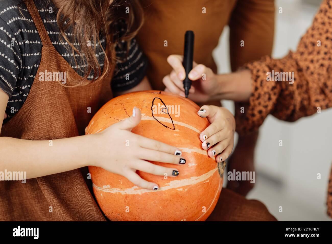 jeune fille assise à une table, décorant des citrouilles. Les vacances d'Halloween et le style de vie de famille. Petite fille peint une citrouille pour Halloween Banque D'Images