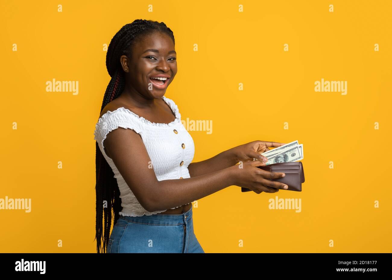 Finance, investissement et économies d'argent. Bonne femme noire mettant des billets dans un portefeuille Banque D'Images