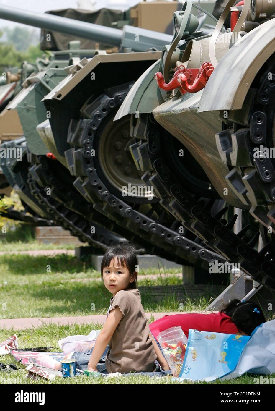 Un enfant est assis à côté d'un char utilisé pendant la guerre de Corée, au musée de la guerre de Corée à Séoul le jour du souvenir le 6 juin 2007. Techniquement, la Corée du Sud et la Corée du Nord sont toujours en guerre, parce que leur conflit de 1950-53 s'est terminé par une trêve armée qui n'a jamais été convertie en traité de paix. REUTERS/JO Yong-Hak (CORÉE DU SUD) Banque D'Images