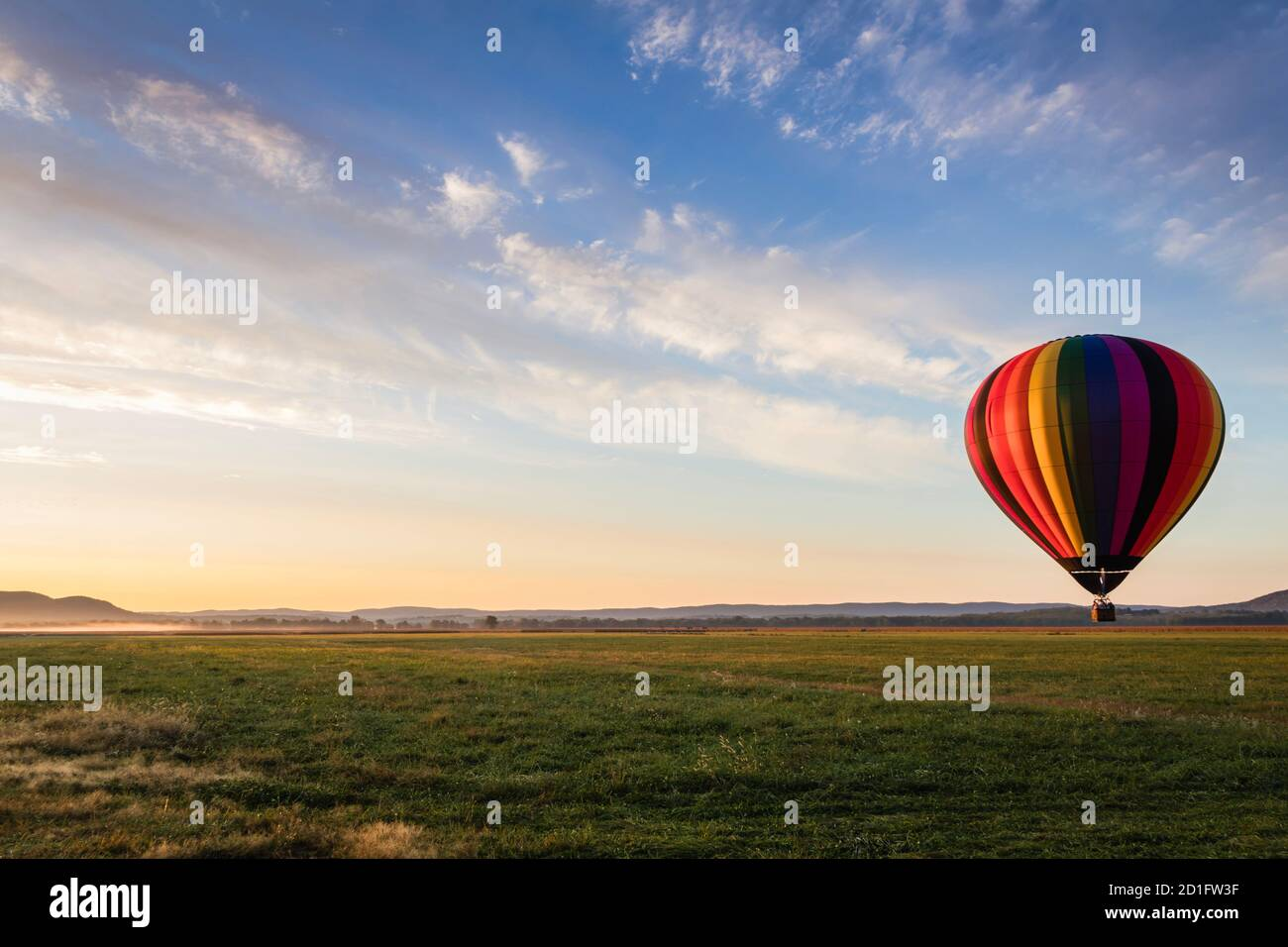 Le ballon d'air chaud dans des bandes arc-en-ciel colorées commence l'ascension champ de ferme au soleil se lève ciel bleu ciel nuageux Banque D'Images
