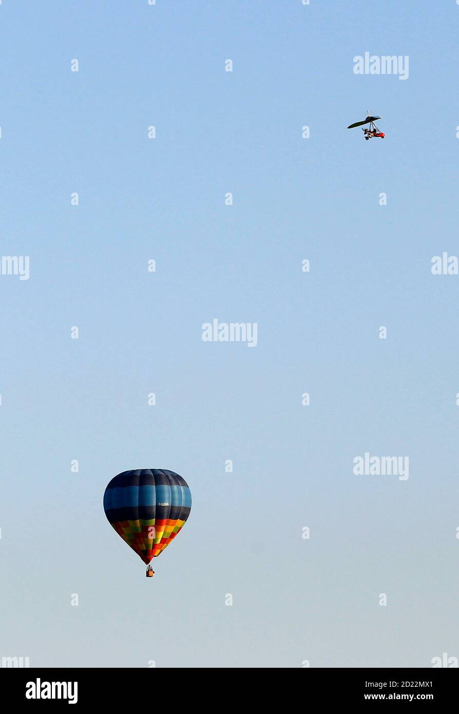 An ultralight aircraft flies near a hot air balloon over Alessandria May 22, 2010.   REUTERS/Alessandro Bianchi   (ITALY - Tags: SOCIETY TRANSPORT) Banque D'Images