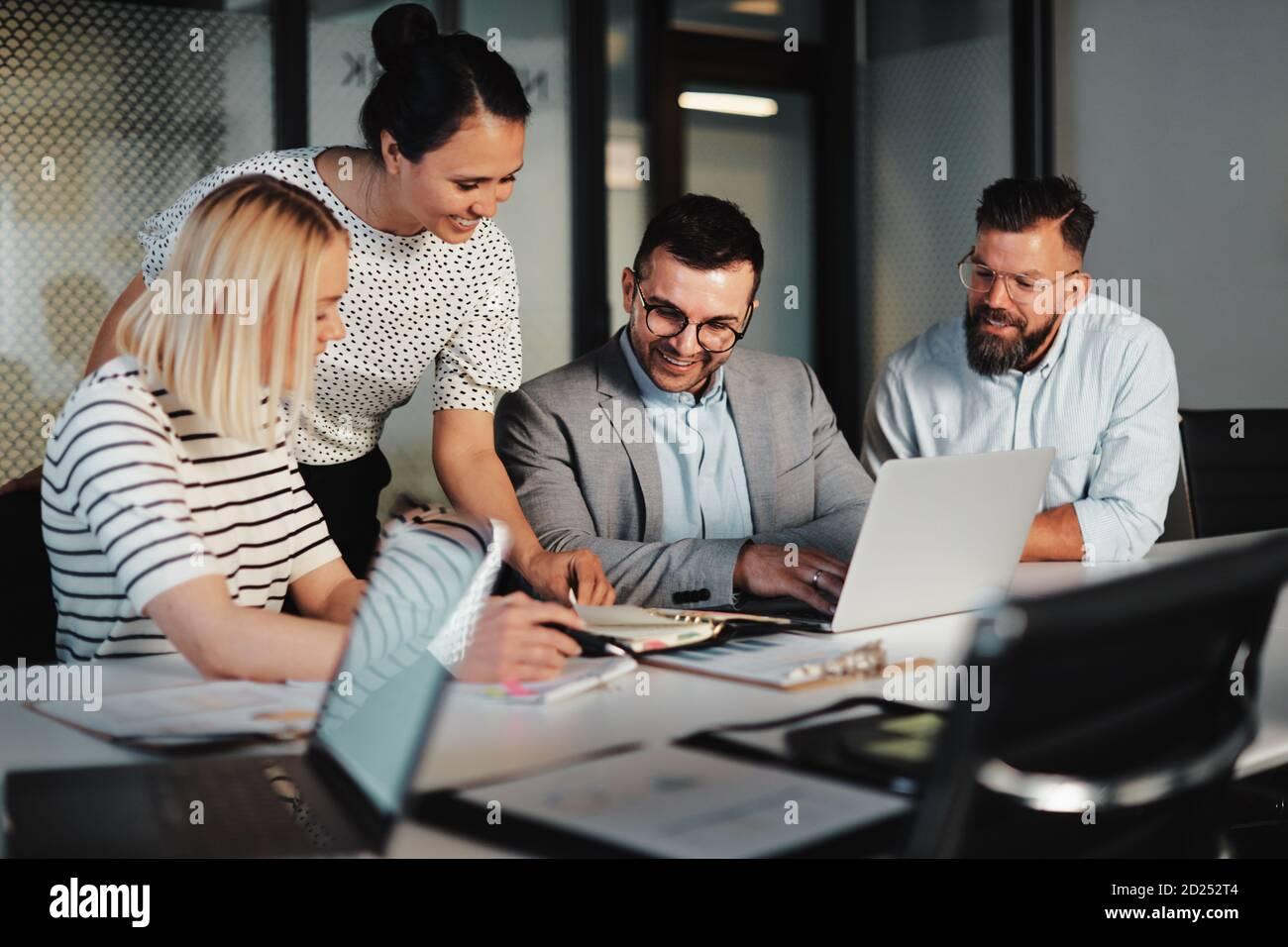 Un groupe souriant de gens d'affaires discutant ensemble à une table pendant une réunion dans une salle de réunion de bureau Banque D'Images