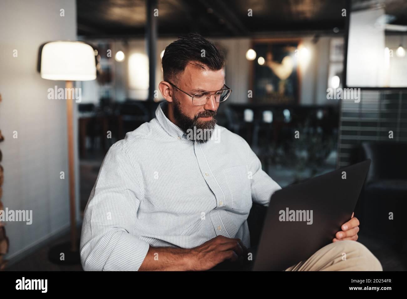 Jeune homme d'affaires travaillant en ligne avec un ordinateur portable tout en étant assis le salon d'un bureau moderne Banque D'Images