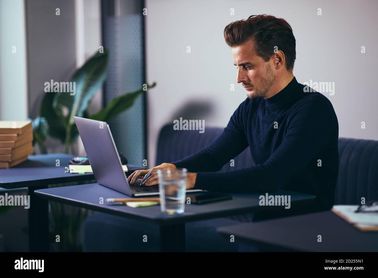 Jeune homme d'affaires concentré travaillant sur un ordinateur portable tout en étant assis à un bureau dans un espace de bureau partagé Banque D'Images