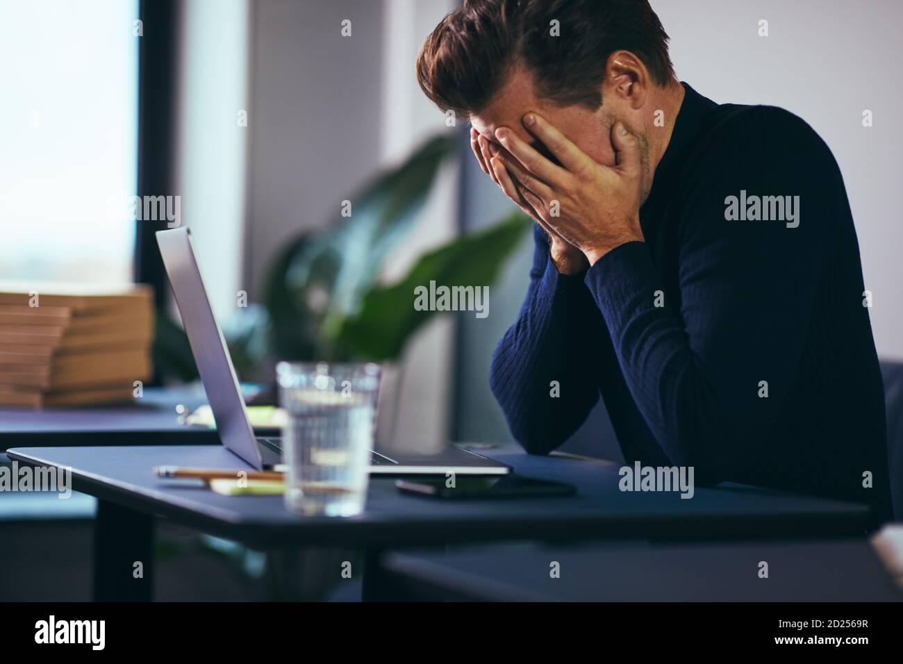 Jeune homme d'affaires assis avec sa tête dans les mains frustration en travaillant sur un ordinateur portable à un bureau Banque D'Images