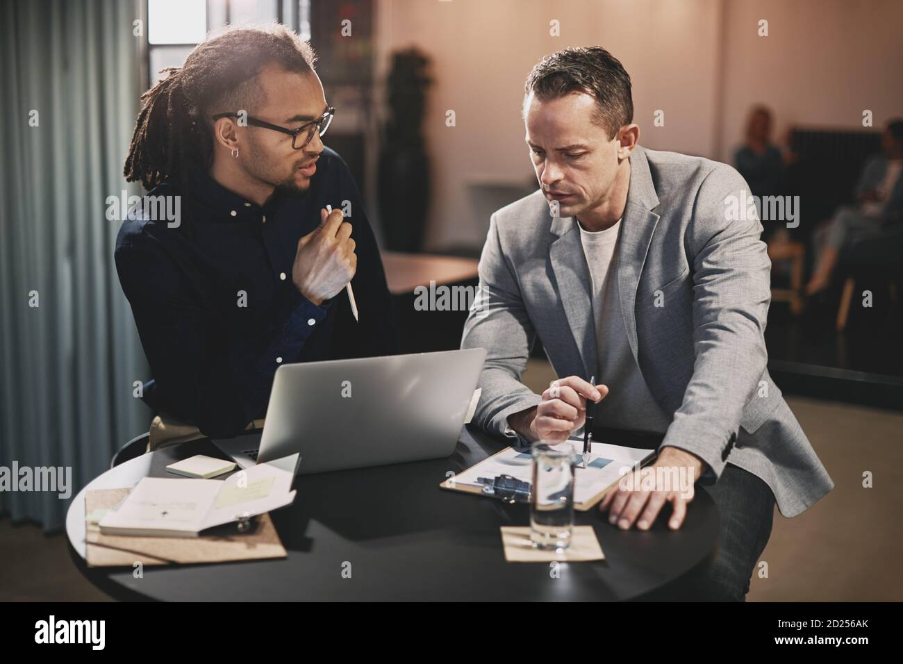 Deux hommes d'affaires différents parlent ensemble sur un ordinateur portable tout en travaillant à une table dans un bureau Banque D'Images