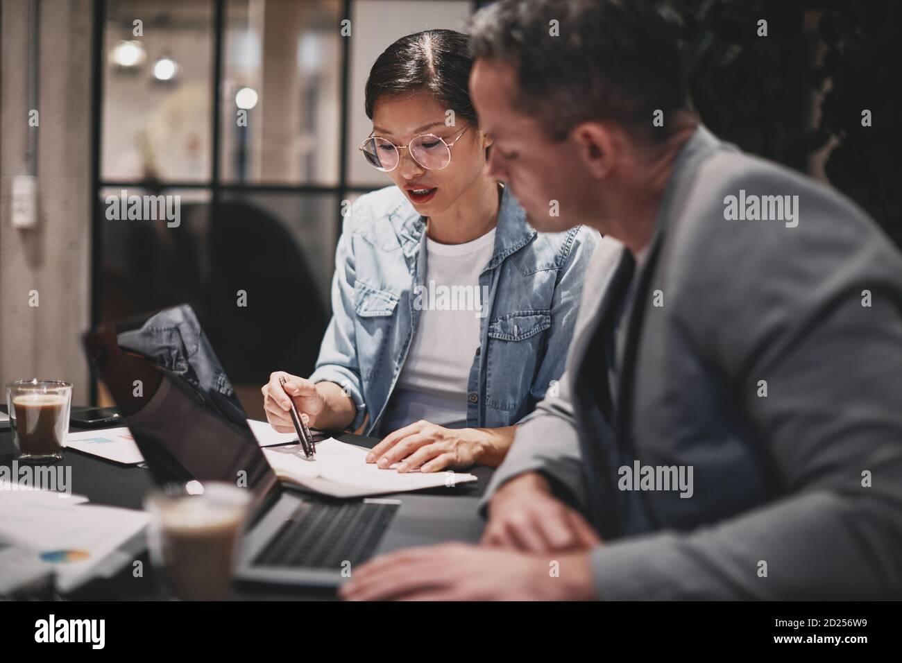 Deux hommes d'affaires divers qui travaillent ensemble sur des documents administratifs une table dans un bureau Banque D'Images