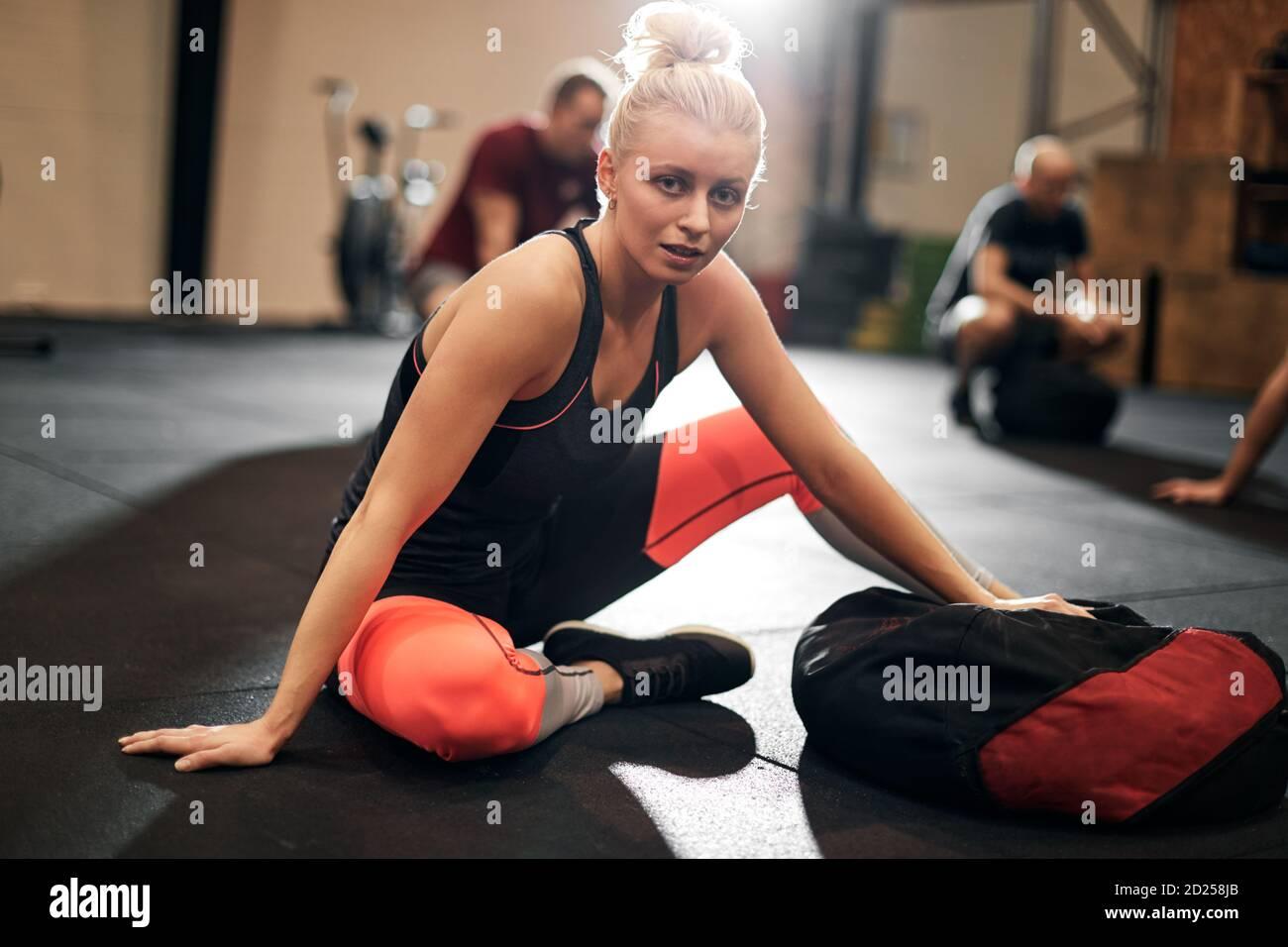 Mettre en forme une jeune femme dans des vêtements de sport assis sur un sol de salle de sport après un cours d'exercice avec un sac de poids Banque D'Images