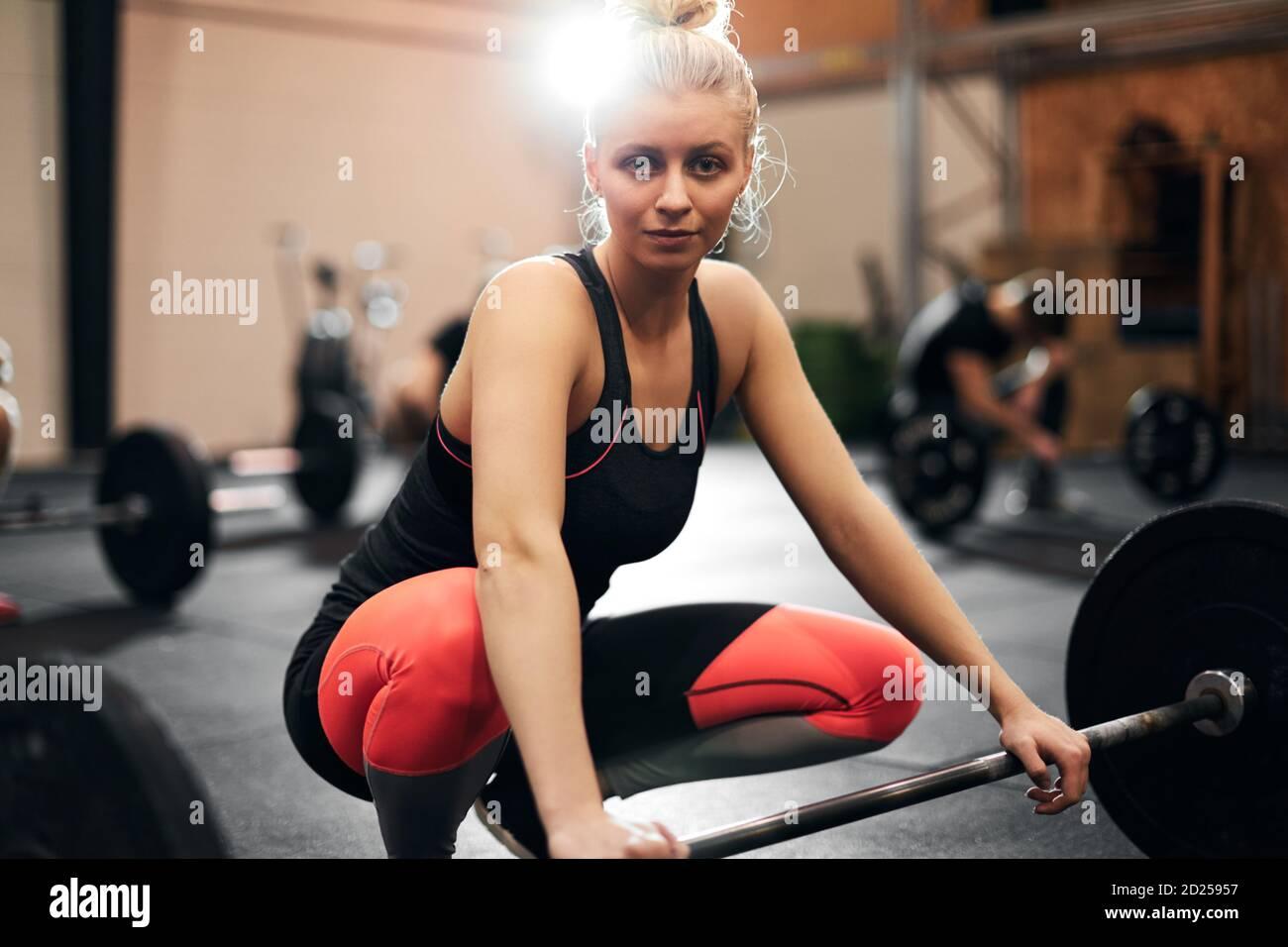 Mettre la jeune femme dans les vêtements de sport se préparant à soulever un peu lourd poids pendant un cours de musculation à la salle de gym Banque D'Images