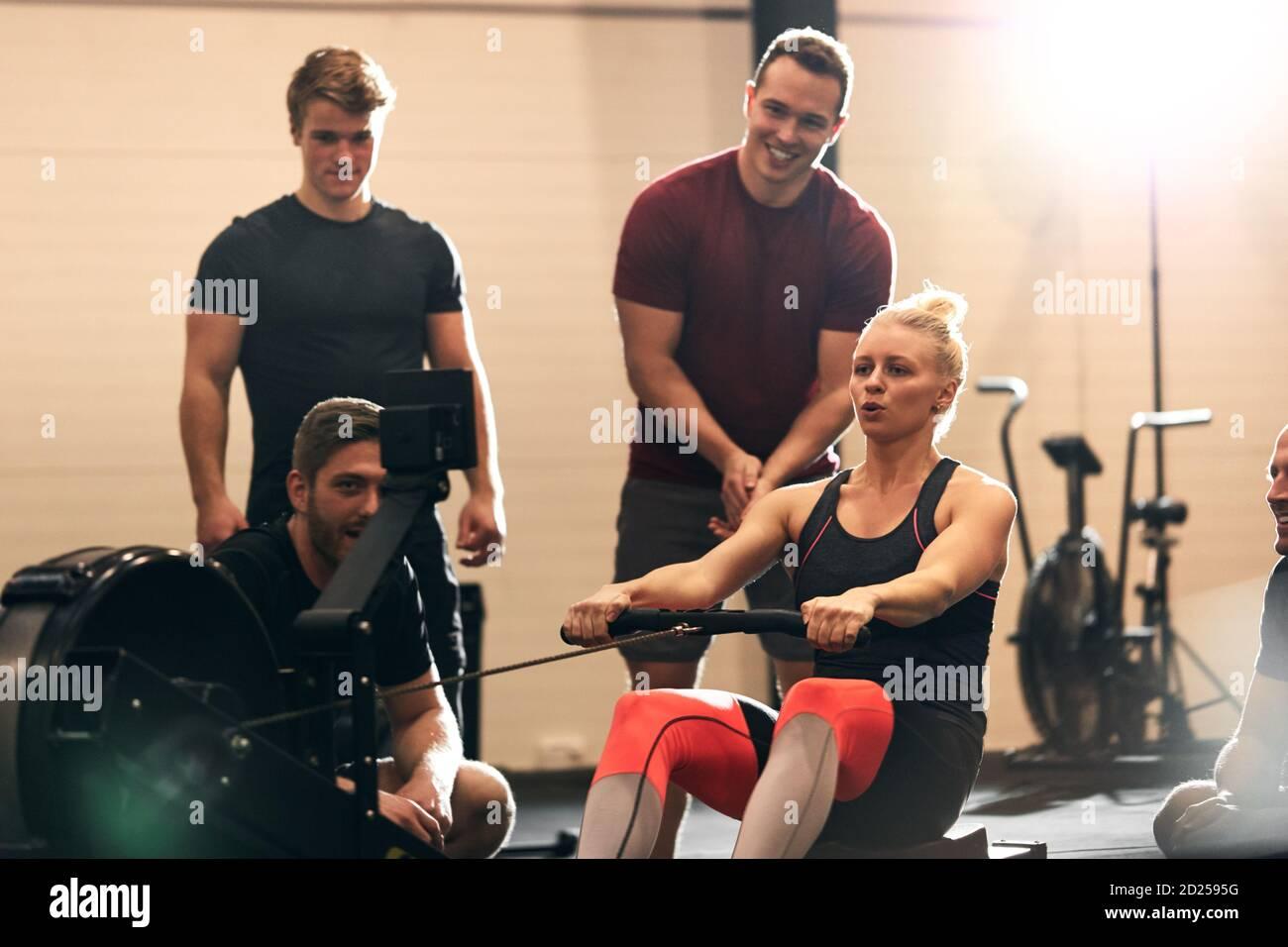 Mettre en forme la jeune femme étant soutenue par ses amis souriants de gym pendant un entraînement sur une machine à ramer Banque D'Images