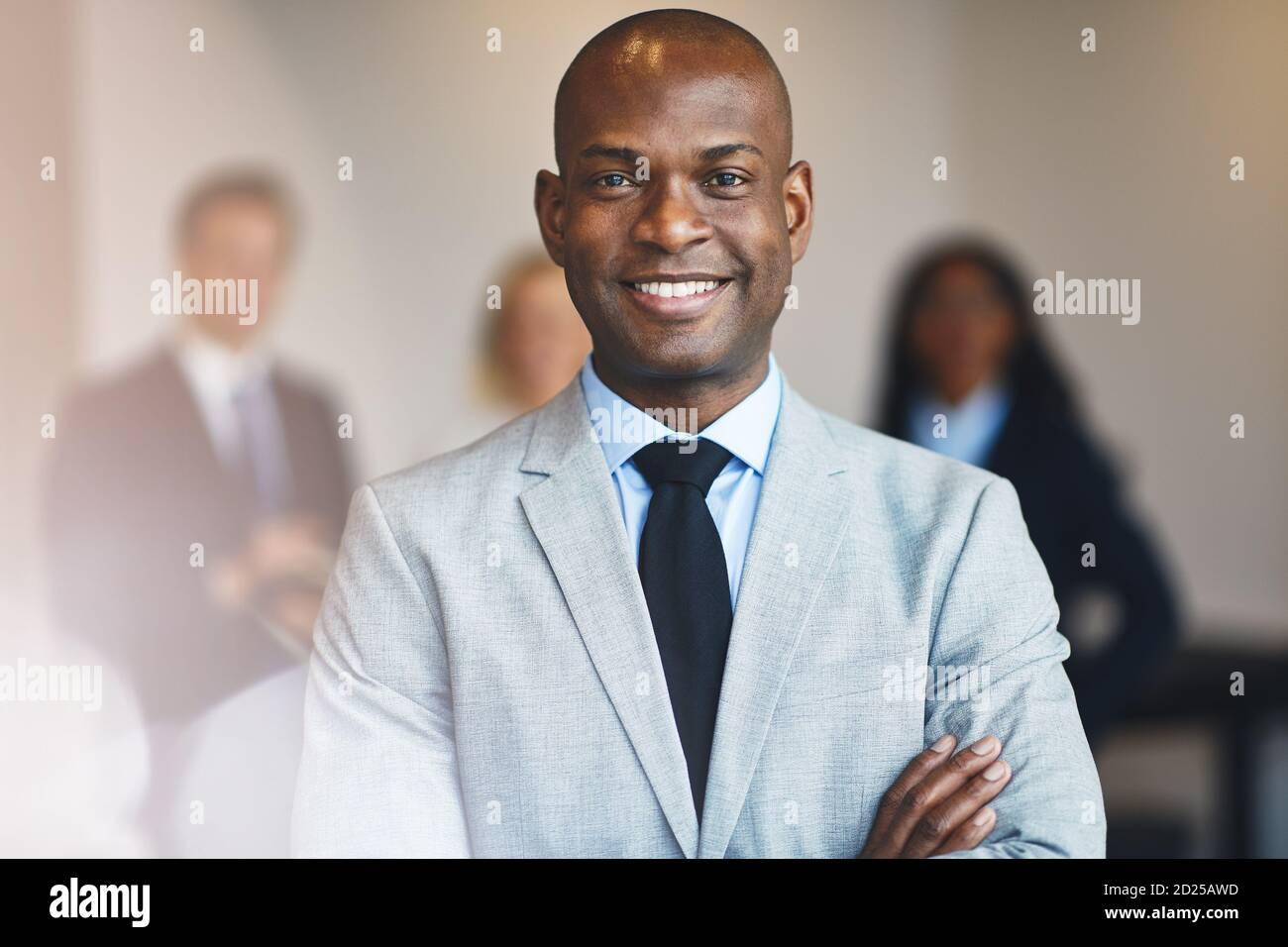 Un jeune homme d'affaires africain souriant debout avec ses bras croisés un bureau avec des collègues debout en arrière-plan Banque D'Images