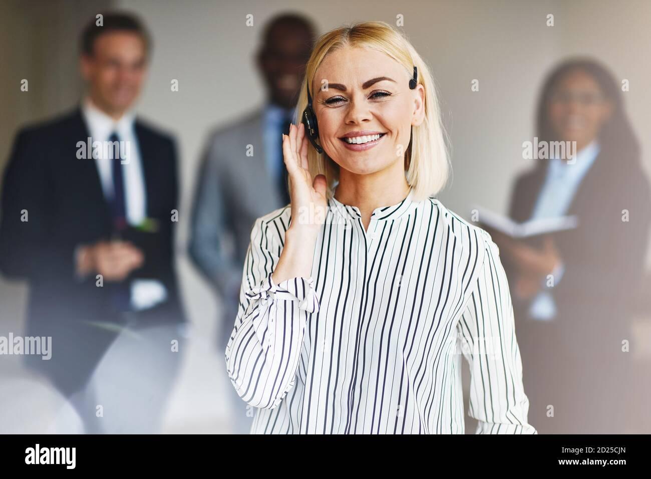 Jeune femme d'affaires portant un micro-casque et souriant lorsqu'elle se tient debout un bureau avec divers collègues en arrière-plan Banque D'Images
