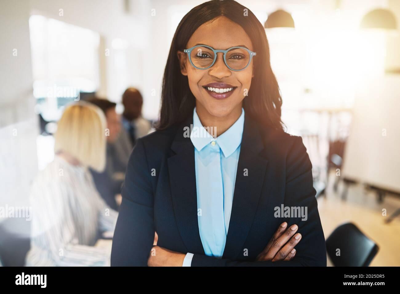 Une jeune femme d'affaires africaine debout avec ses bras a traversé une salle de réunion de bureau et sourire avec des collègues en arrière-plan Banque D'Images