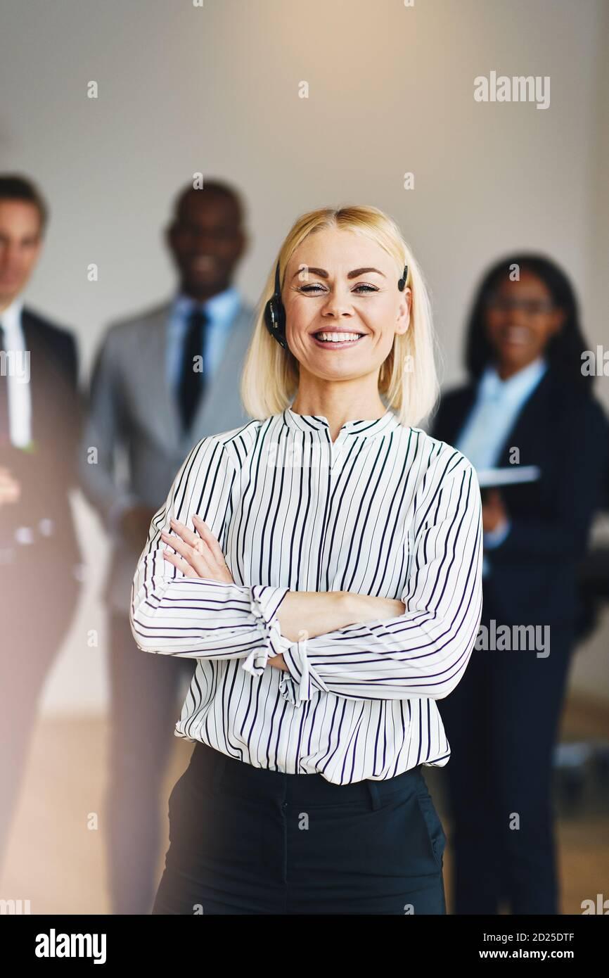 Jeune femme d'affaires souriante debout dans un bureau avec une diverse groupe de collègues debout en arrière-plan Banque D'Images