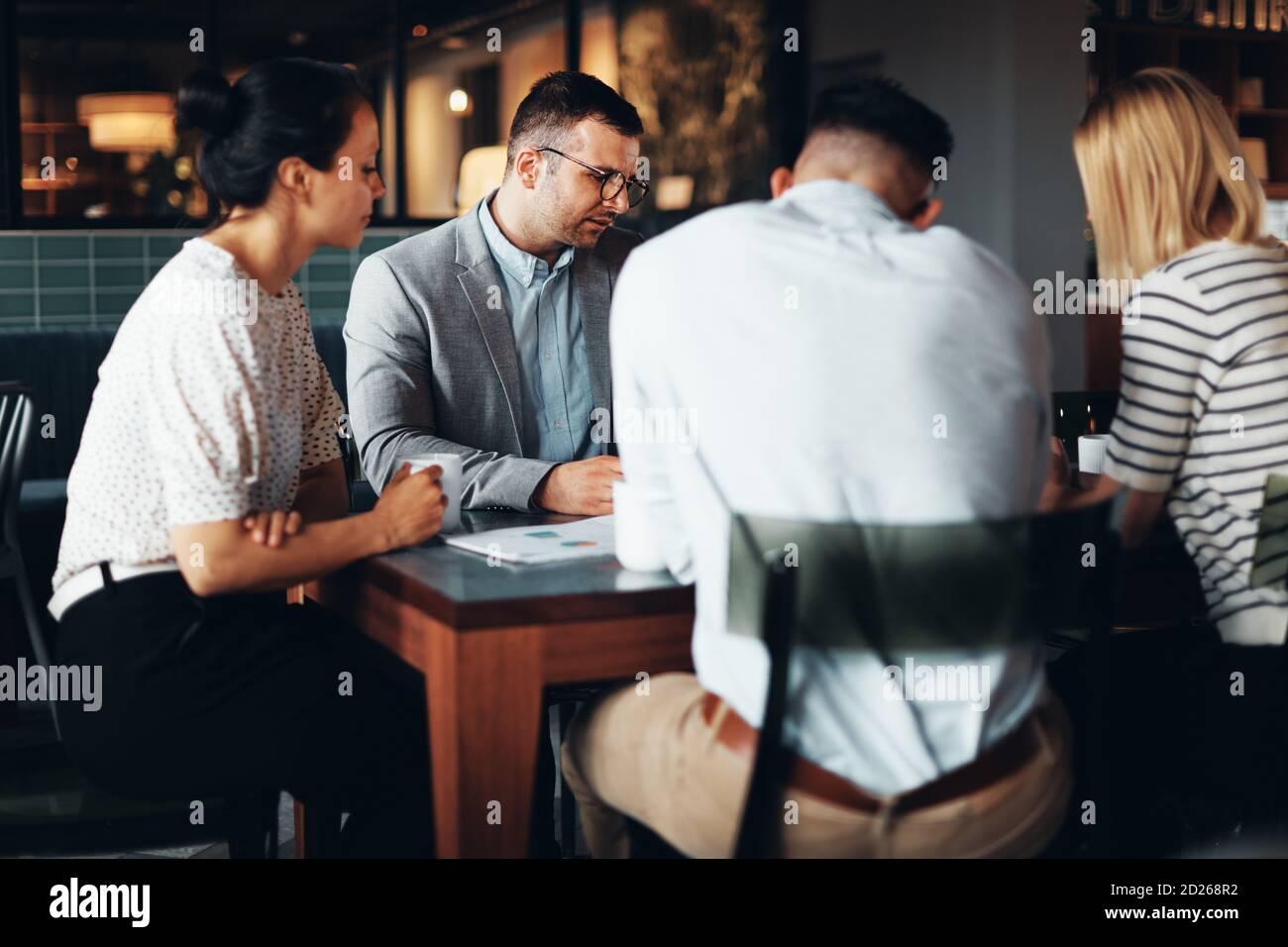 Groupe d'hommes d'affaires qui se mêle à la paperasse pendant leur café pause dans le salon d'un bureau Banque D'Images