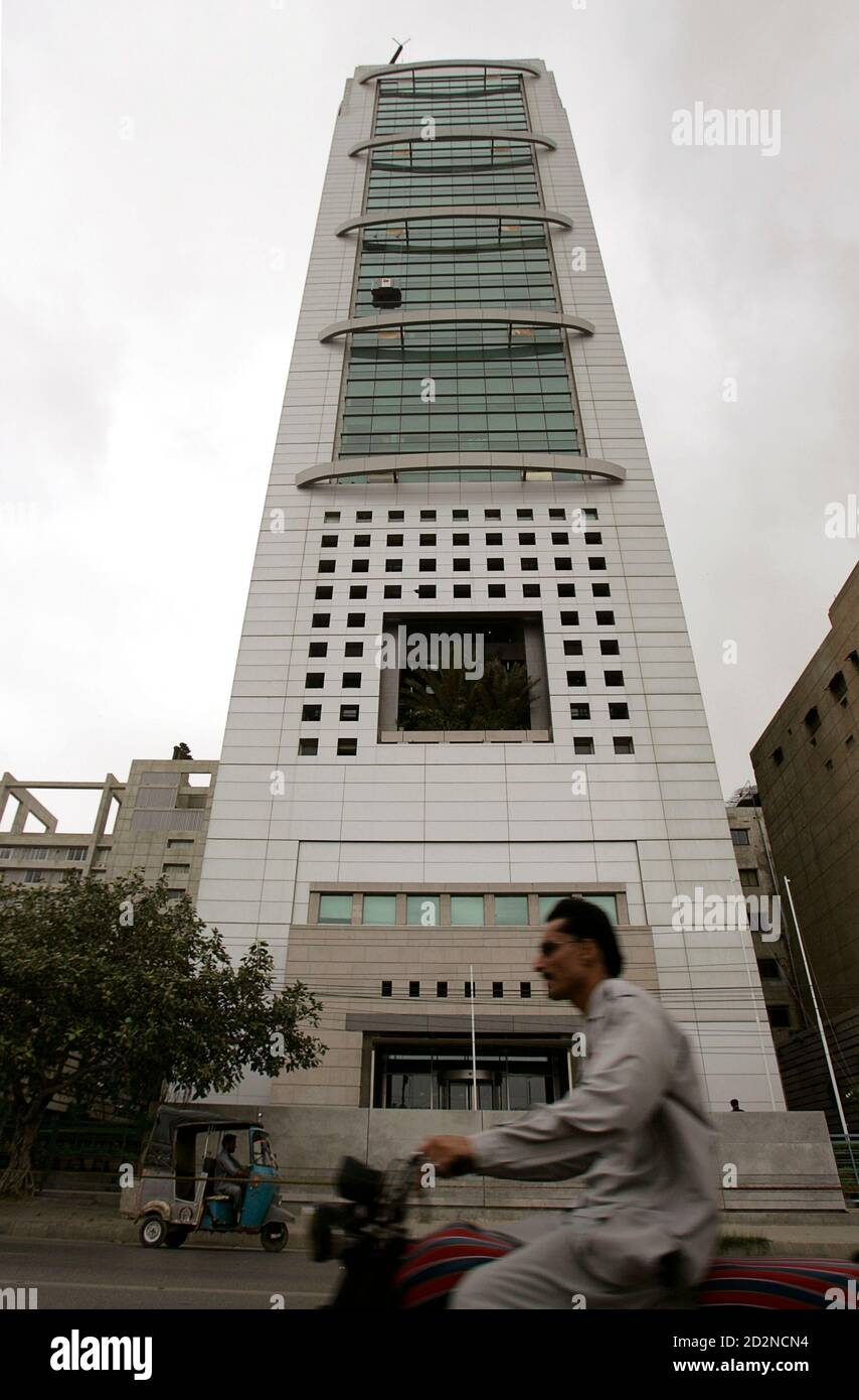Commuters ride past the front of the MCB Bank tower in Karachi's business district on August 10, 2009. MCB, Pakistan's largest bank, will pay around $90 million to acquire the local operations of the Royal Bank of Scotland (RBS), a source with direct knowledge of the deal said on Monday. REUTERS/Akhtar Soomro (PAKISTAN BUSINESS) Banque D'Images