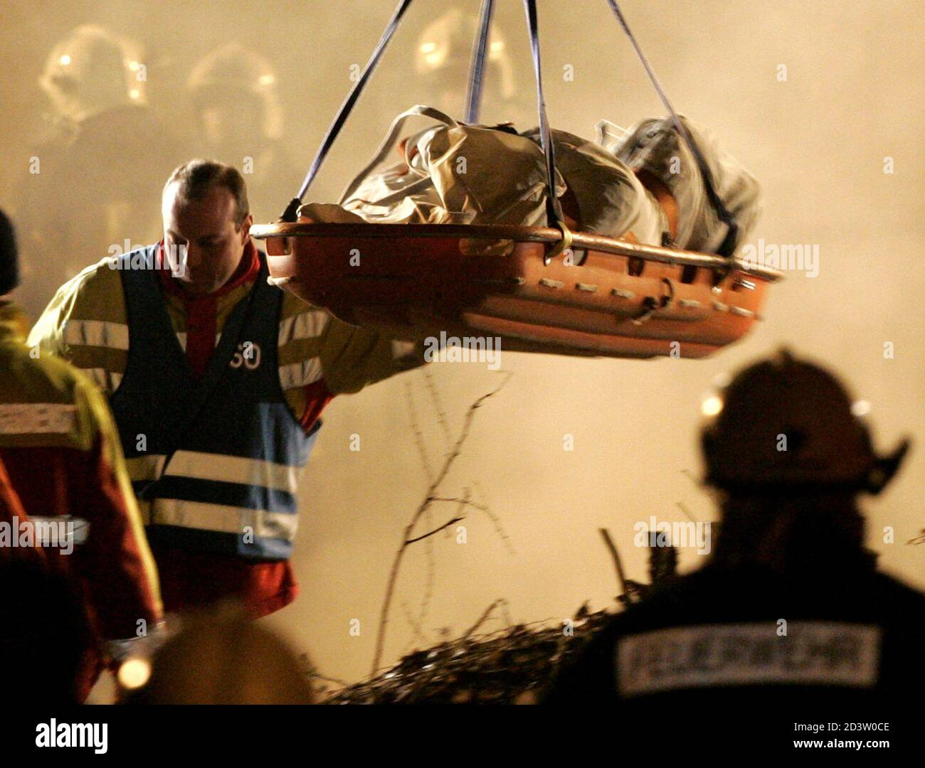 The body of a firefighter is lifted from an underground car park after the roof collapsed and buried up to seven fire fighters in the town of Gretzenbach between the cities of Basel and Zurich November 27, 2004. Construction experts, earthquake rescue specialists and other fire and rescue personnel raced against time to find the men who had been battling a fire in the residential car park when the roof caved in and trapped them in its rubble. Pictures of the month November 2004 REUTERS/Ruben Sprich  RS/WS Banque D'Images