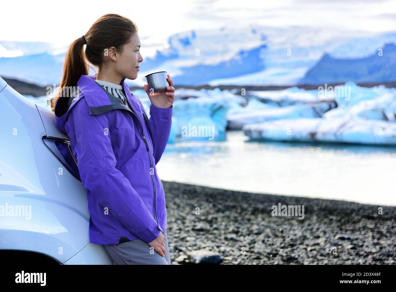 Camping camping-car. Femme buvant un café le matin devant le camping-car tout en conduisant une camionnette de camping sur la route de l'Islande. Chauffeur touristique asiatique Banque D'Images