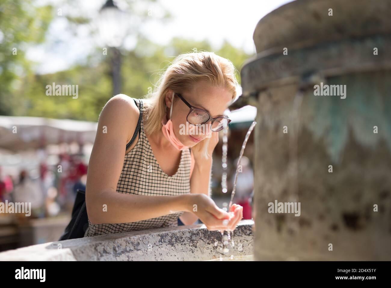 Une jeune femme cucasienne décontractée assoiffée portant un masque médical pour boire de l'eau de la fontaine publique de la ville par une chaude journée d'été. Nouvelles normes sociales pendant Banque D'Images