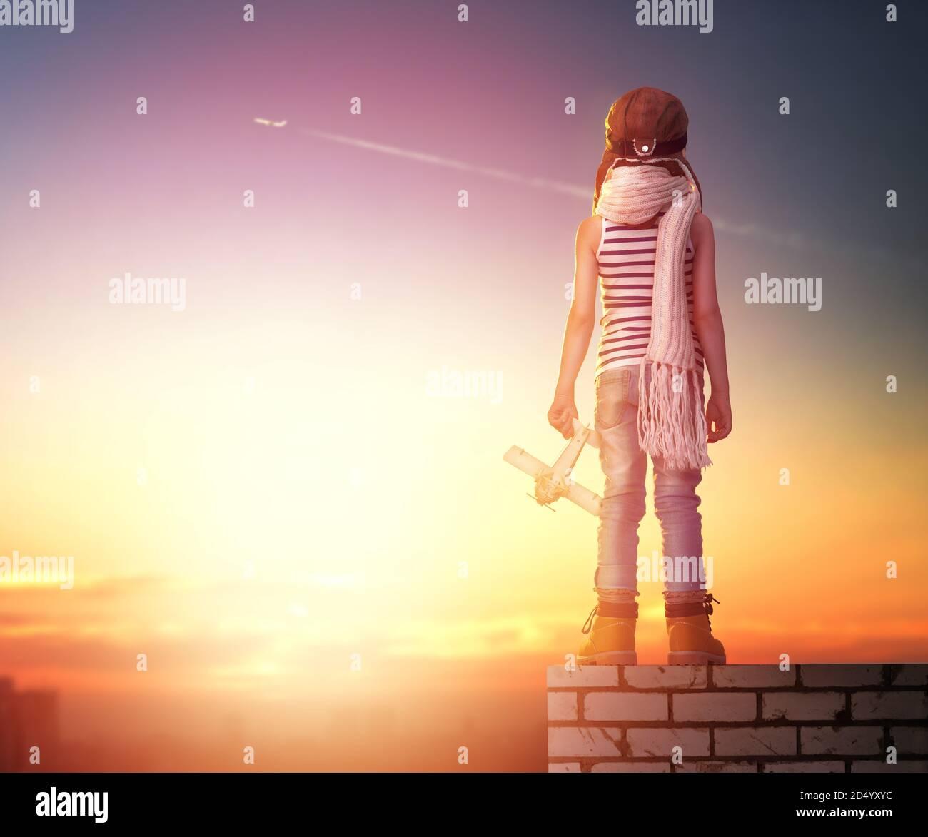 un enfant joue avec un avion jouet au coucher du soleil et rêve de devenir pilote Banque D'Images
