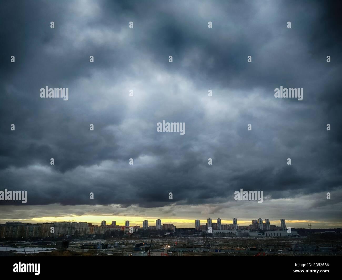Une tempête suronde la ville. Ciel noir dans les nuages et la ligne du coucher de soleil orange. Zone industrielle sur fond de bourdes imminentes Banque D'Images