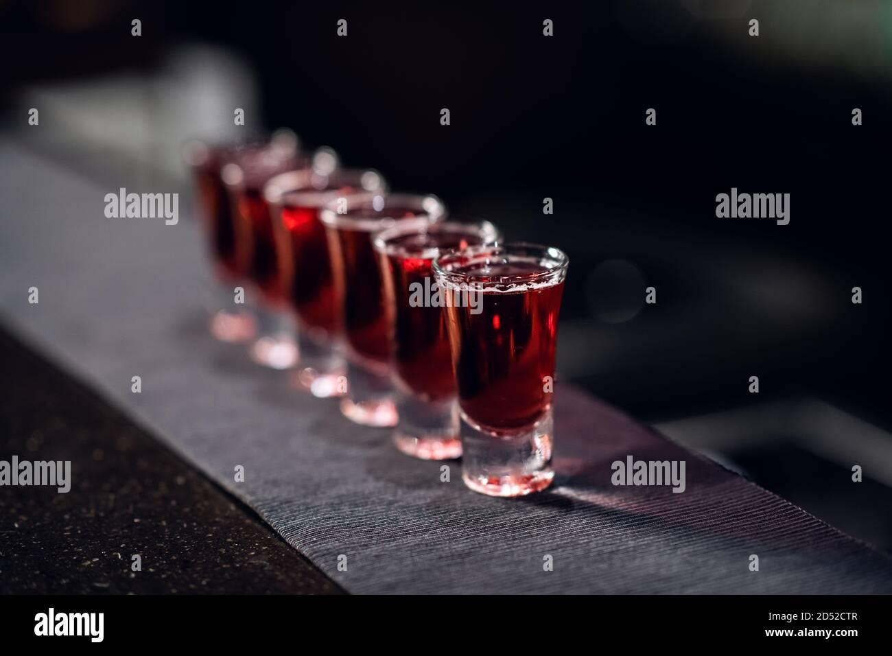 une rangée de prises de vue avec de la liqueur rouge sur le bar du tissu en gros plan. Banque D'Images