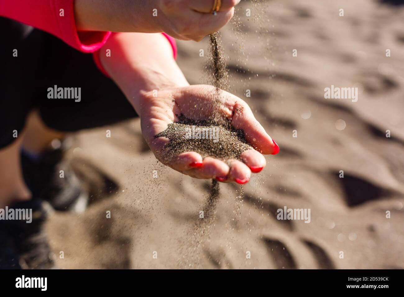 la main verse le sable au bord de la mer et les rochers. symbole pour le temps qui s'écoule et la gestion du temps. ongles avec manucure. Banque D'Images